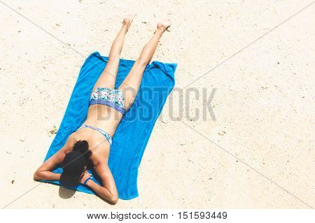 Top view and copy space of slim woman is lying sunbathe on the beach