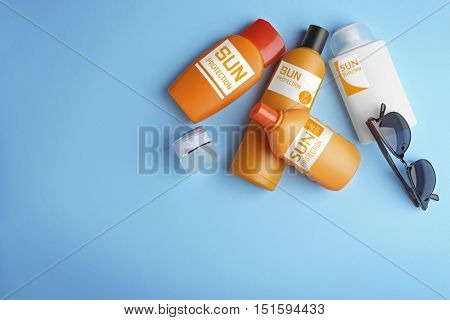 Sun protection creams on blue background, top view
