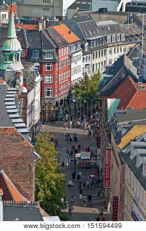 Copenhagen Denmark - August 5 2010: People strolling through the pedestrianized streets of Copenhagen's central shopping district below the colourful buildings and roofs.