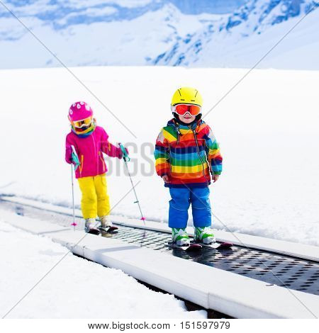 Children on magic carpet ski lift going uphill in the mountains on snowy winter day. Kids in winter sport school in alpine resort. Family fun in the snow. Little skier exercising on a slope.