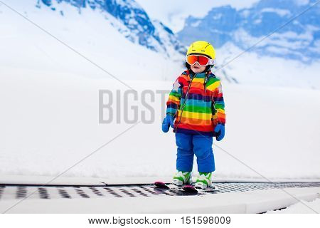 Child in alpine ski school with magic carpet lift and colorful training cones going downhill in the mountains on a sunny winter day. Little skier kid learning and exercising skiing on a slope.