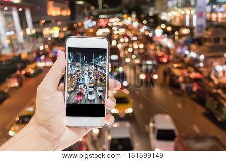 Blurry Focus Close up of Hand is holding button on phone to take photos at night traffic on road , view from on overpass