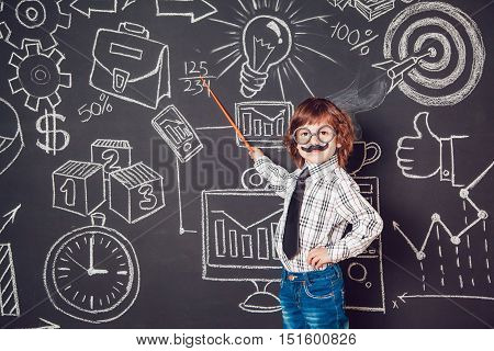 Little boy as businessman or teacher with mustache and glasses standing on a dark background pattern. Wearing shirt and tie