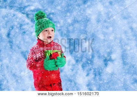 Little girl and boy in red and green knitted hat holding Christmas present boxes in winter park on Xmas eve. Kids play outdoor in snowy winter forest. Children opening presents. Panorama banner.