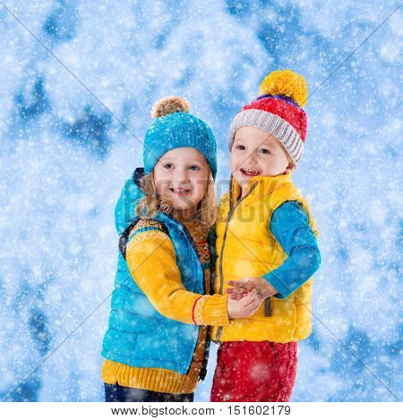 Little girl and boy in yellow and blue knitted hat catching snowflakes in winter park on Christmas eve. Kids play outdoor in snowy winter forest. Children catch snow flake on Xmas. Toddler kid playing