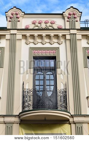 Wrought-iron balcony of a historic building in Art Nouveau style adorned with decorative floral elements.