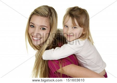 Beautiful Young Blonde Woman Giving a Little Girl a Piggy Back Ride on a White Background