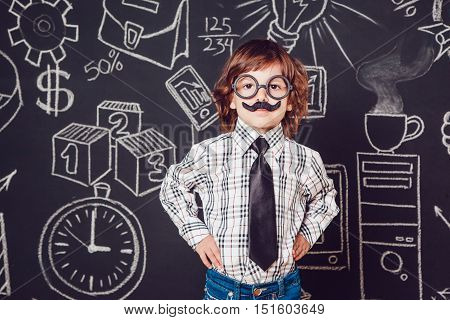Little boy as businessman or teacher with mustache and glasses standing her hands folded on a dark background pattern