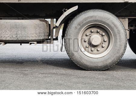 Dirty wheels of lorry on gray asphalt road