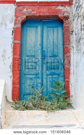 The porch and the old, cracked, blue, wooden door in abandoned house. Fira. Santorini