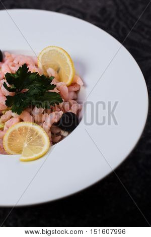 Shrimps with olives and lemon on white plate
