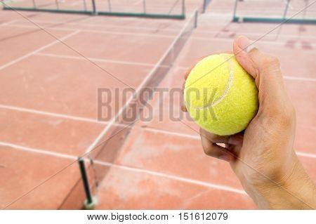 hand catching tennis ball with tennis stadium background