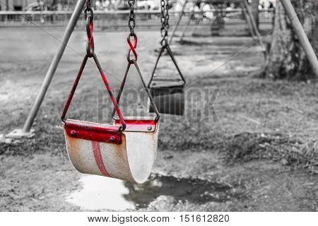 old red swing at playground . selective colored effect . background with copy space for message concept .