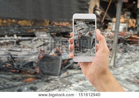 man photographing the damages of the home affected by the fire for home insurance