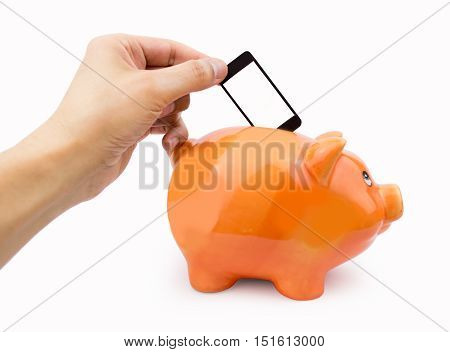 hand putting the cellphone into the piggy bank as concept saving with mobile fee