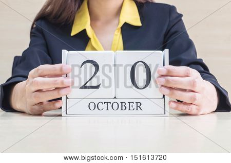 Closeup white wooden calendar with black 20 october word in blurred working woman hand on wood desk in office room selective focus at the calendar