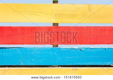 detail of wooden fence painted in colors in horizontal