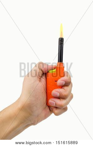 hand pressing the button of orange gas lighter for kitchen with flame
