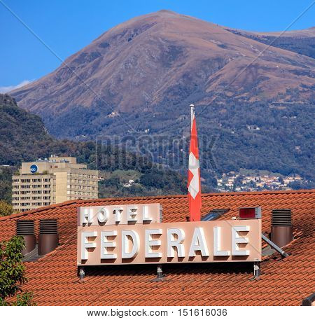 Lugano, Switzerland - 12 October, 2016: roof of the Hotel Federale building with sign and flag of Switzerland. Hotel Federale is a three stars hotel, located in the center of Lugano, which is the largest city in the Swiss canton of Ticino.