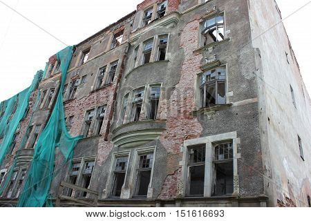 Abandoned destroyed old residential apartment housing building facade. Damaged house in need of renovation. Brick walls texture