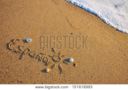 Spain sign on the sand beach with the sea wave