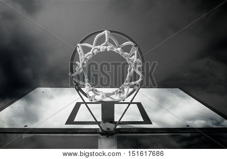 view from down of the basketball hoop with sky background in black and white