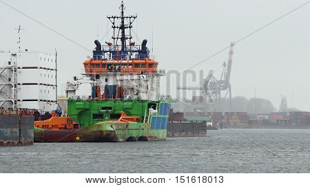 Tugboat Docked in Port with Cargo Containers. Large harbor cranes loading and unloading container ships in the port of Rotterdam. Industrial container freight trade port scene.