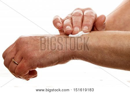 senior female rubbing her wrist with a white pain relieving cream