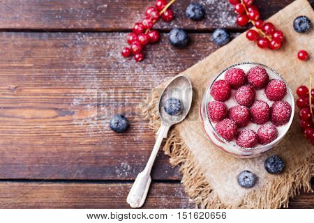 Raspberry dessert, cheesecake, trifle, mouse in a glass on a wooden background.Top view Copy space