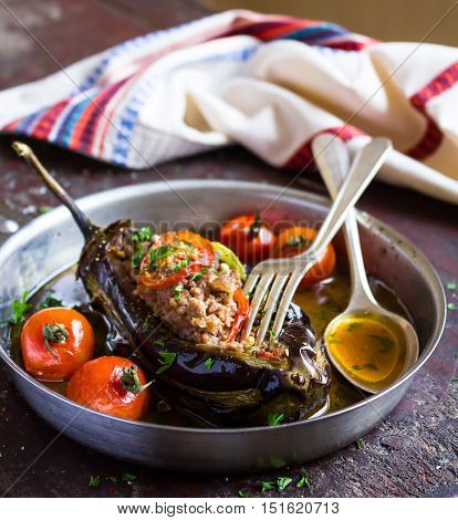 Stuffed eggplant or aubergine with minced meat, carrot, onion, cherry tomatoes, pepper in a pan, traditional turkish cuisine, selective focus