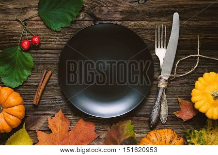 Autumn table setting for Thanksgiving dinner, Halloween. Blank black plate, fork and knife, pumpkins and fallen leaves on wooden table. Top view