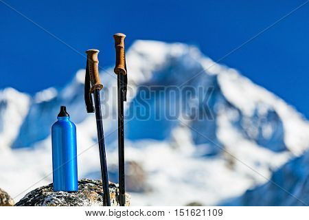 Hiking Gear over Himalaya Mountains Background. Travel Equipment Trekking Stick and Water Bottle in Inspirational High Himalayas Landscape over Blue Sky in Nepal.
