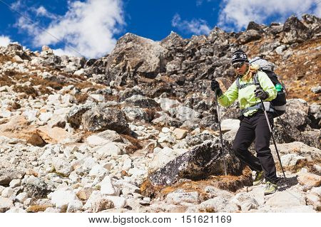 Woman hiker trekking with big backpack in Himalaya Mountains on Rocky Trail. Girl on hiking trail in high mountains travel and expedition in inspirational mountain landscape with beautiful views.