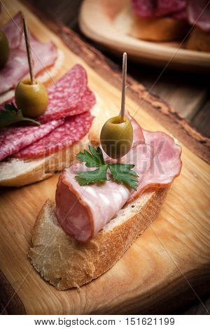 Tapas With Sliced Sausage, Salami, Olives And Parsley.