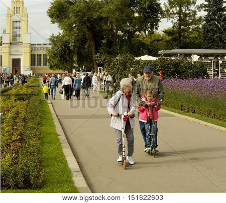 MOSCOW, RUSSIA - September 10, 2016: Pre-adolescent girl and senior adult woman and man ride on scooters in the Park ENEA. September 10, 2016 in Moscow, Russia