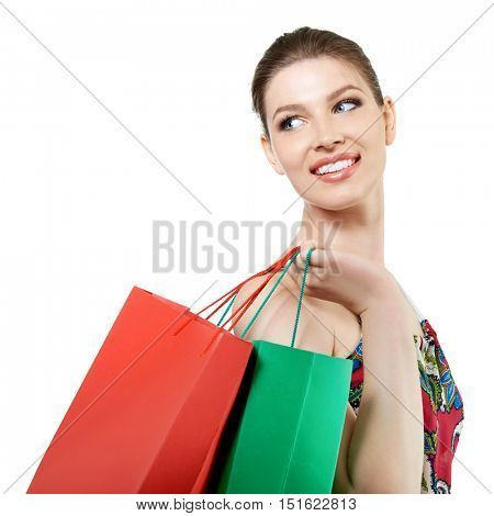 Shopping woman holding shopping bags looking at copy space. Beautiful young female shopper smiling happy, isolated on white.