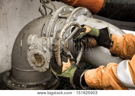 Man in safety gloves and orange coverall is opening/closing pipe valve