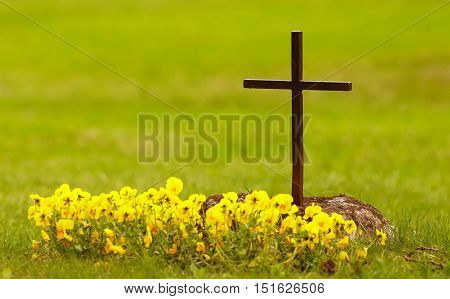 Christian grave with yellow flowers planted at the grave.