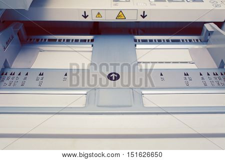 Paper tray in the printer. Printing machine construction part