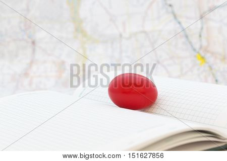 Red egg on ledger pages with map behind shows troubled financial and business times. Selective focus on key nest egg symbol.