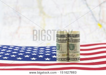 American dollars placed on USA flag with distant map as background. Economic growth is a national issue.