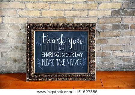 Chalk board framed in an elegant vintage picture frame gives message to wedding guests thanking them for attending and giving them a favor.
