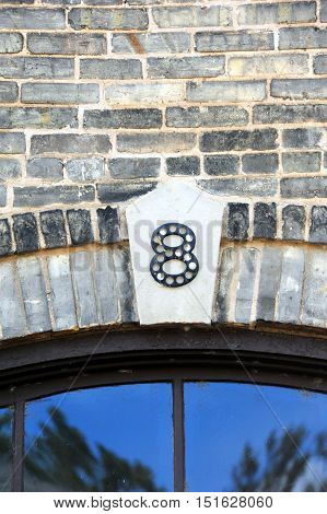 The letter 8 is composed of steel and mounted on an old brick wall on the outside of an old tobacco wharehouse in Wisconsin.