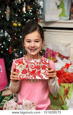 Little girl holds a gift from her grandmother and smiles. It is Christmas morning and she is surrounded by presents.