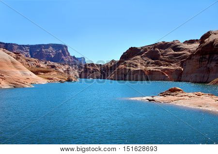 Aqua waters of Lake Powell curve away into the distant Glen Canyhon National Recreation Area. Rock mounds and steep cliffs rise on either side.