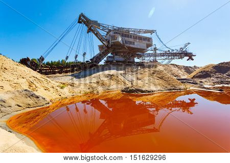 multi bucket excavator, giant stacker, absetzer in career. red water rich in minerals