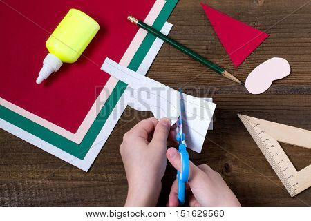 Creating a Christmas decoration for table setting. Decor for serviette in form of Santa Claus. Children project step by step photo instructions. Step 3. The child cuts out the details