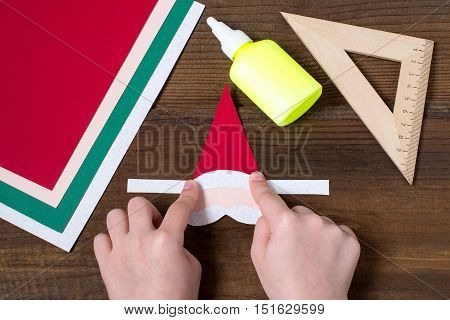 Creating a Christmas decoration for table setting. Decor for serviette in form of Santa Claus. Children project step by step photo instructions. Step 5. The child glues the parts of Santa Claus