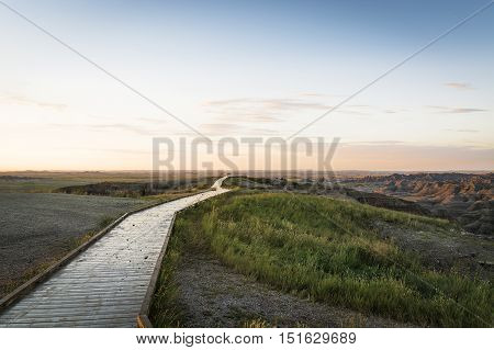 wooden walkway between sand and grass at sunset