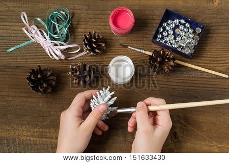 Making Christmas decorations from pine cones. Children project step by step photo instructions. Step 2. Child paints a white acrylic paint pine cone